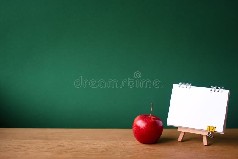 Назад к концепции школы, открытой тетради на миниатюрном мольберте и красному яблоку на деревянной поверхности на фоне чистого зе стоковые изображения