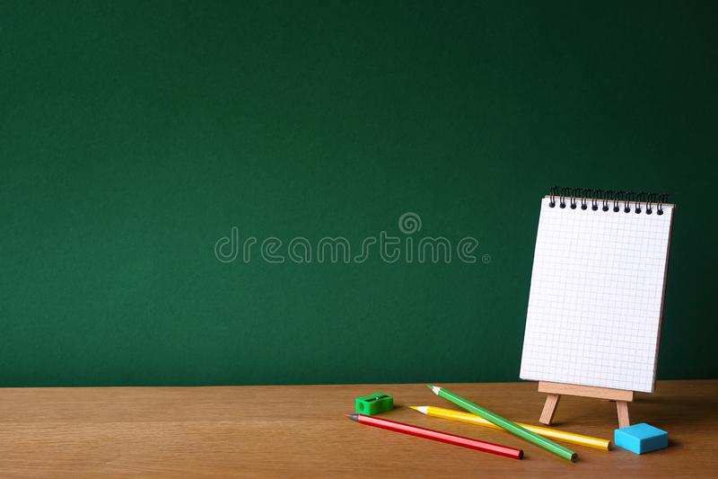 Назад к концепции школы, открытой тетради на миниатюрном мольберте и нескольким покрашенных карандашей на деревянной поверхности  стоковые изображения