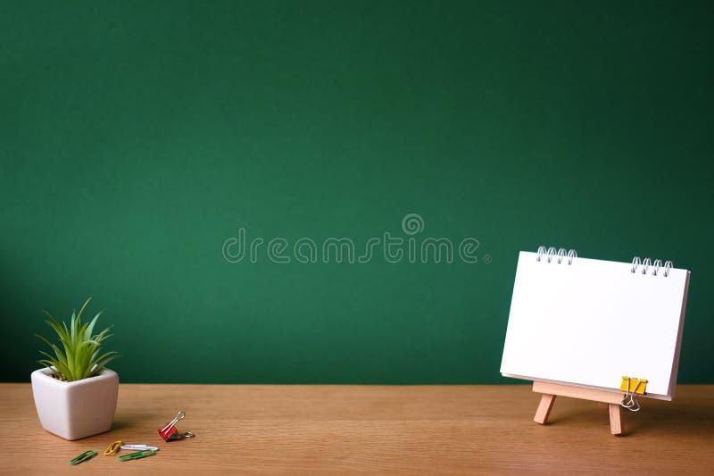 Назад к концепции школы, открытой тетради на миниатюрном мольберте и небольшому суккулентному в белом баке на деревянной поверхно стоковая фотография rf