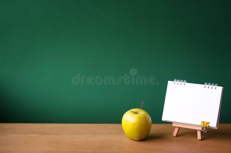 Назад к концепции школы, открытой тетради на миниатюрном мольберте и зеленому яблоку на деревянной поверхности на фоне чистого зе стоковые изображения