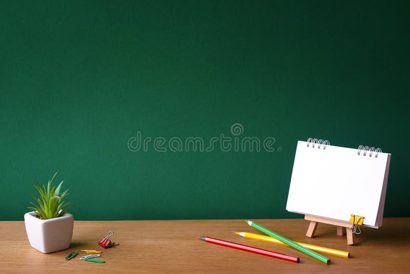 Назад к концепции школы, открытым тетради на миниатюрном мольберте, суккулентному в баке и покрашенных карандашах на деревянной п стоковое изображение
