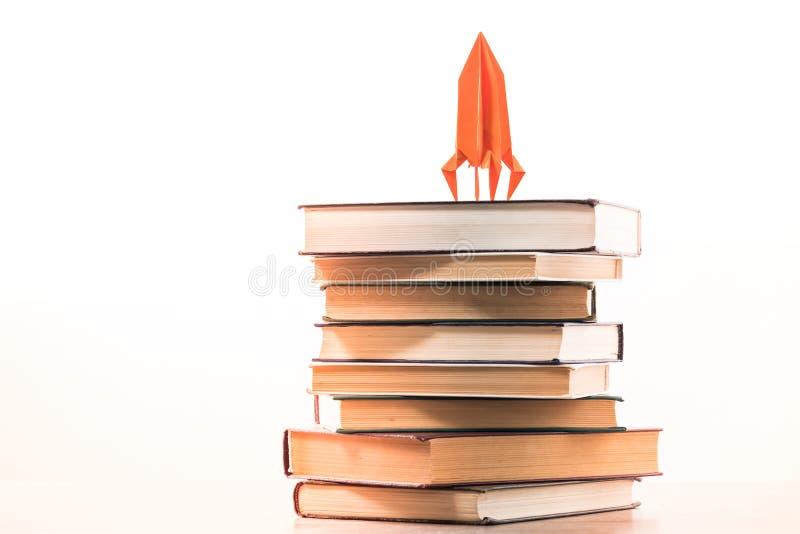 Назад к концепции школы ракета на книгах Идея знания и устремленностей в карьере, белой предпосылке стоковое фото rf