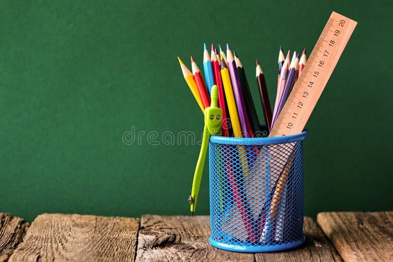 Назад к концепции школы, синее стекло со школьными принадлежностями на старой деревянной поверхности на предпосылке чистой зелено стоковые фото