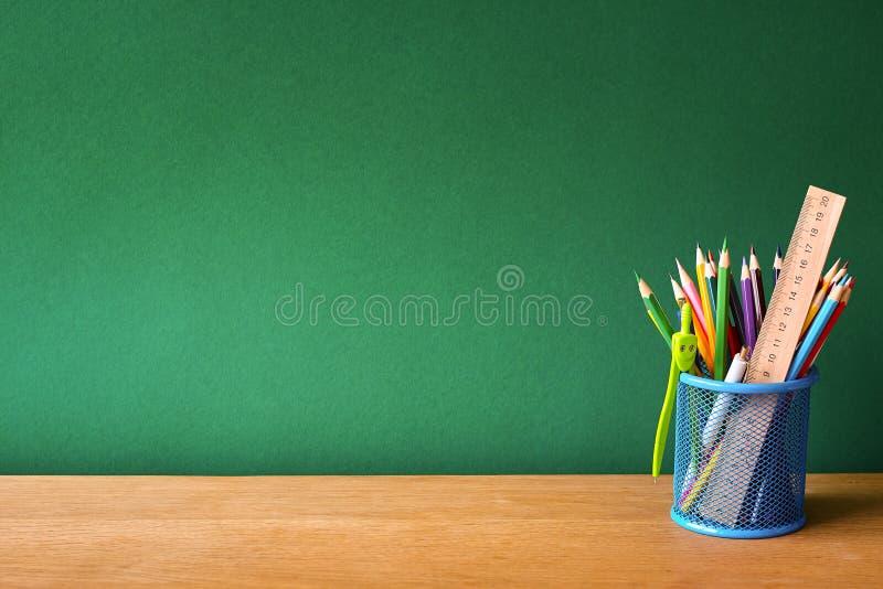 Назад к концепции школы, синее стекло со школьными принадлежностями на столе школы на предпосылке чистой зеленой доски мела, выбо стоковое изображение