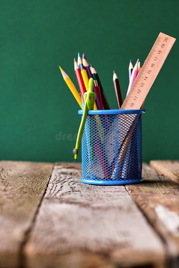 Назад к концепции школы, синее стекло со школьными принадлежностями на столе школы на предпосылке чистой зеленой доски мела, выбо стоковые изображения rf
