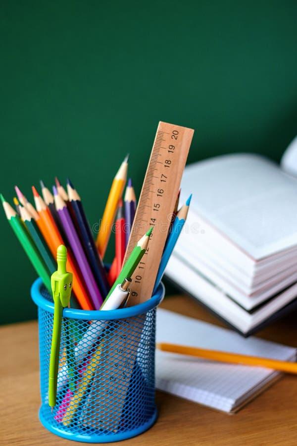 Назад к концепции школы, синему стеклу со школьными принадлежностями, открытому учебнику и тетради на предпосылке чистой зеленой  стоковые изображения rf
