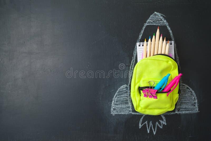 Назад к концепции школы с небольшими рюкзаком сумки, школьными принадлежностями и эскизом ракеты над предпосылкой chalkboad стоковые фото