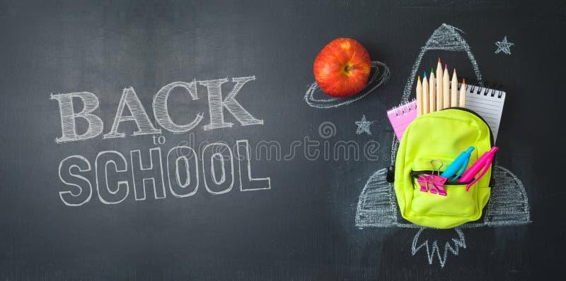 Назад к концепции школы с небольшими рюкзаком сумки, школьными принадлежностями и эскизом ракеты над предпосылкой chalkboad r стоковые фотографии rf