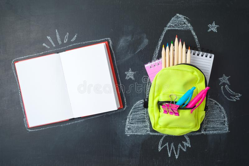 Назад к концепции школы с небольшими рюкзаком сумки, школьными принадлежностями и эскизом ракеты над предпосылкой chalkboad r стоковая фотография rf