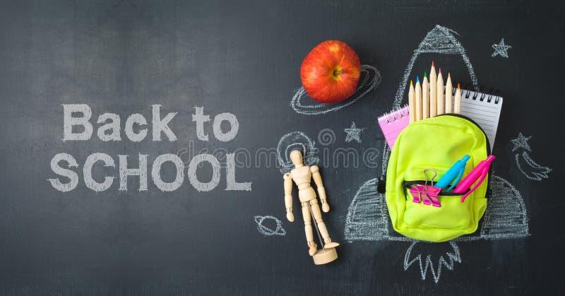 Назад к концепции школы с небольшими рюкзаком сумки, школьными принадлежностями и эскизом ракеты над предпосылкой chalkboad r стоковое изображение rf