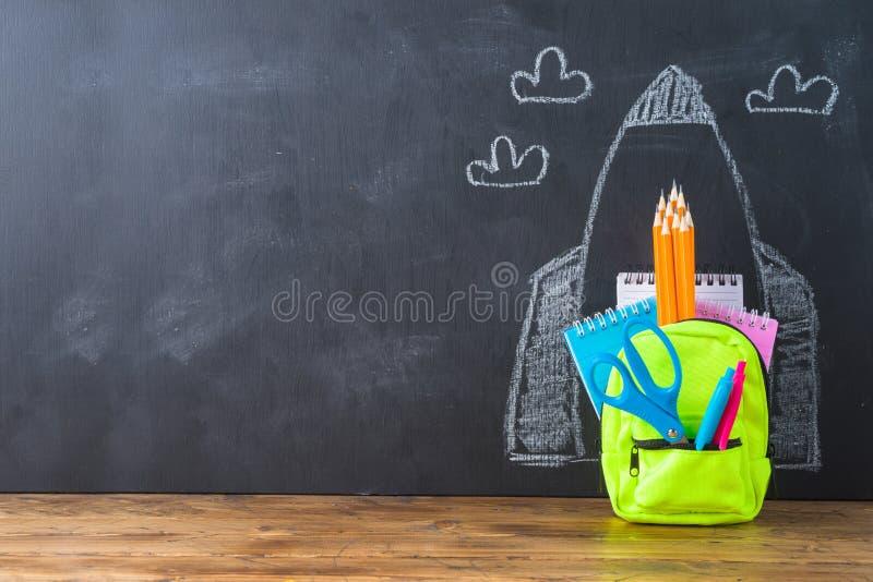 Назад к концепции школы с небольшими рюкзаком сумки, школьными принадлежностями и эскизом ракеты над предпосылкой chalkboad стоковые изображения rf