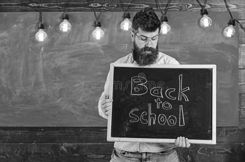 Назад к концепции школы Человек с бородой и усик на удивленных студентах гостеприимсв стороны, доска на предпосылке стоковая фотография rf