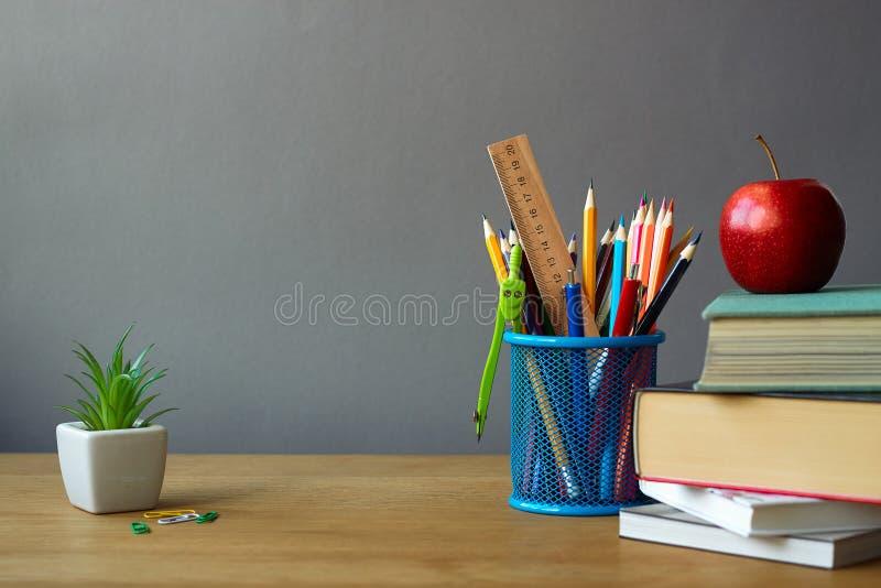Назад к концепции школы, школьные принадлежности, стог книг, красные яблоко и суккулентный в белом баке на деревянной поверхности стоковые изображения