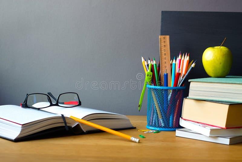 Назад к концепции школы, школьным принадлежностям, стогу книг, доске мела и открытой книге со стеклами на деревянной поверхности, стоковое изображение