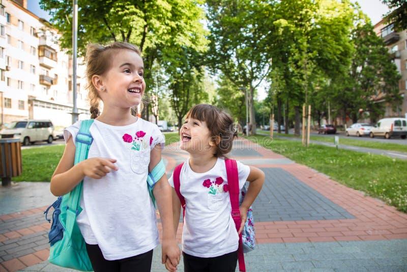 Назад к концепции школьного образования с детьми девушки, элементарные студенты, рюкзаки нося идя классифицировать стоковая фотография rf