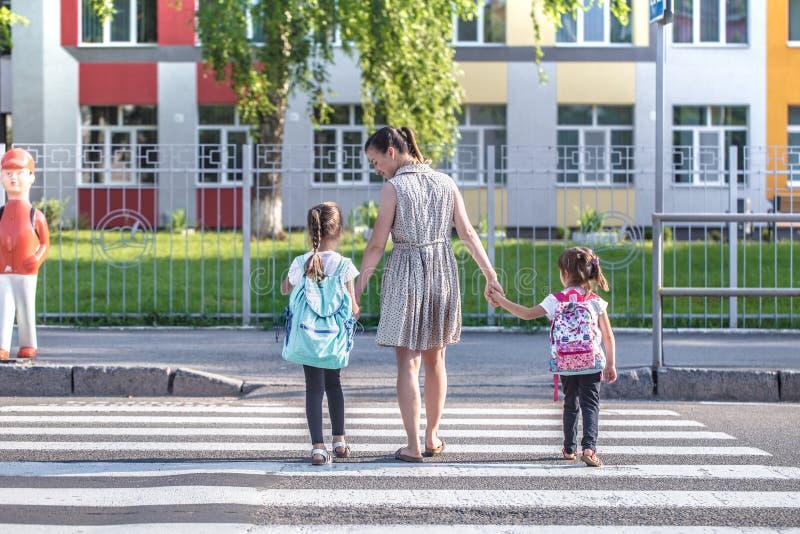 Назад к концепции школьного образования с детьми девушки, элементарные студенты, рюкзаки нося идя классифицировать стоковое фото