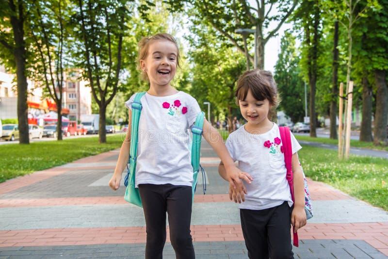 Назад к концепции школьного образования с детьми девушки, элементарные студенты, рюкзаки нося идя классифицировать стоковое фото rf