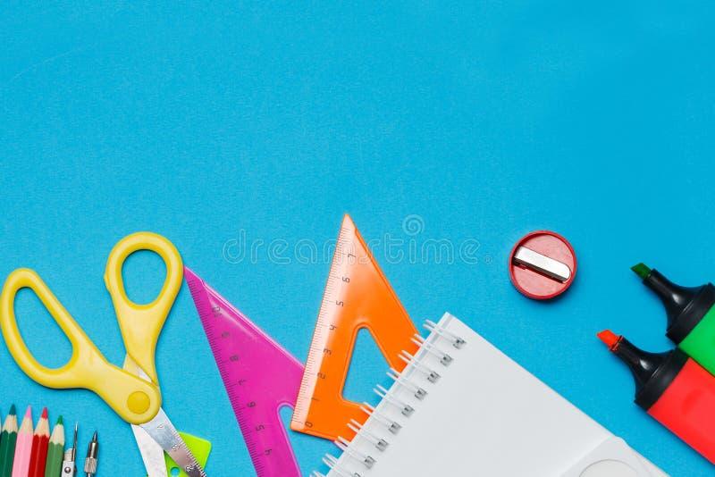 Назад к предпосылке школы с аксессуарами для schoolroom - красками, карандаши, тетради, книги, ножницы, мел, отметки, синь стоковое фото