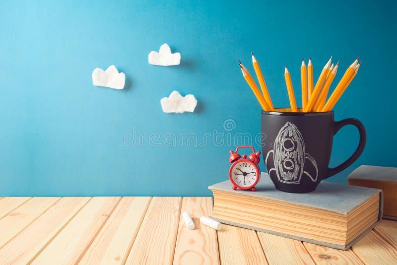 Назад к предпосылке школы с карандашами, эскизом доски ракеты, книгами и будильником на деревянном столе стоковое изображение rf