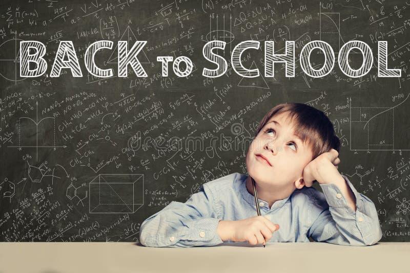 Назад к тексту школы и счастливому ребенк на предпосылке доски стоковые фото