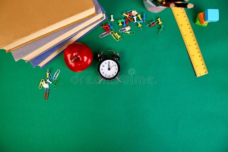 Назад к школьным принадлежностям Книги и красное яблоко на зеленой предпосылке стоковая фотография rf