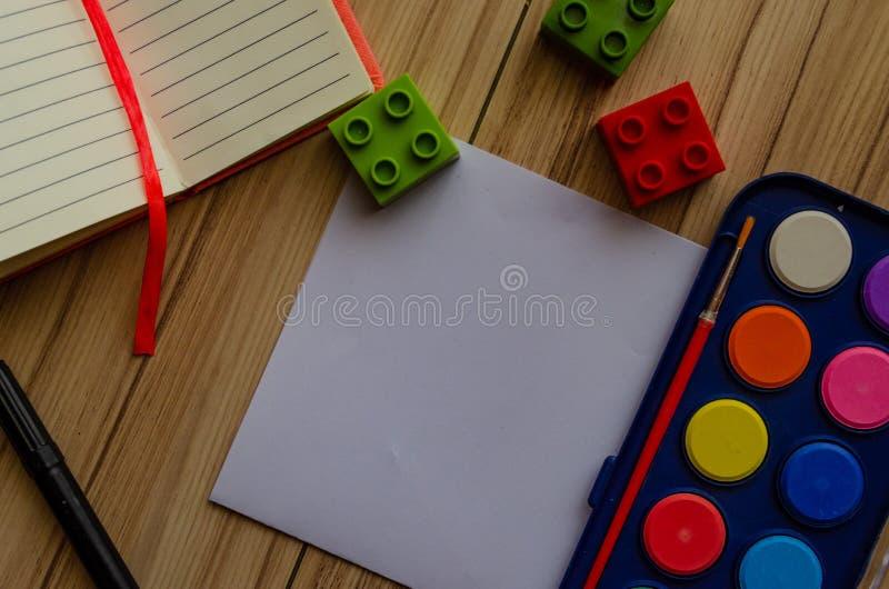 Назад к palet акварели концепции школы плоско положите с чистым листом бумаги и строительными блоками стоковые изображения