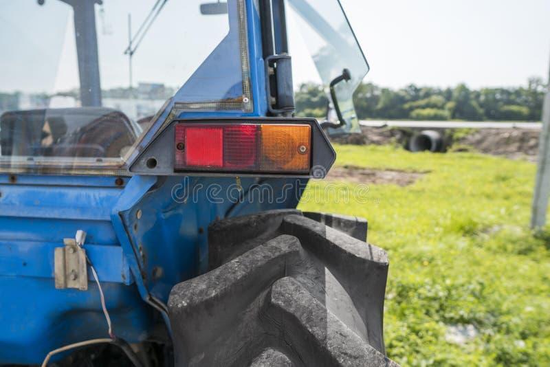 Назад малого мини оранжевого трактора с фокусом на заднем свете стоковая фотография