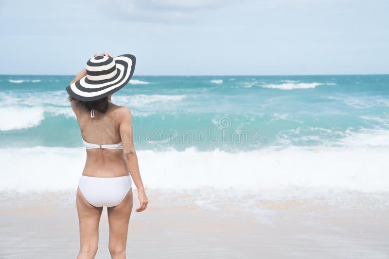 Назад молодой женщины в бикини стоя на пляже, молодая красивая сексуальная женщина в купальнике бикини, тропическом острове, лете стоковые изображения