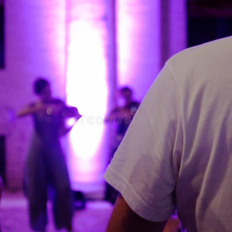 Назад человека в белой рубашке На заднем плане девушка играет скрипку в светах ночи стоковое изображение rf