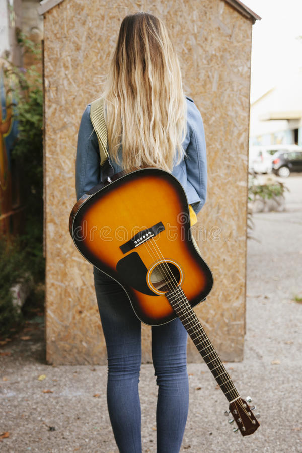 Назад женщины с acustic гитарой стоковые фотографии rf