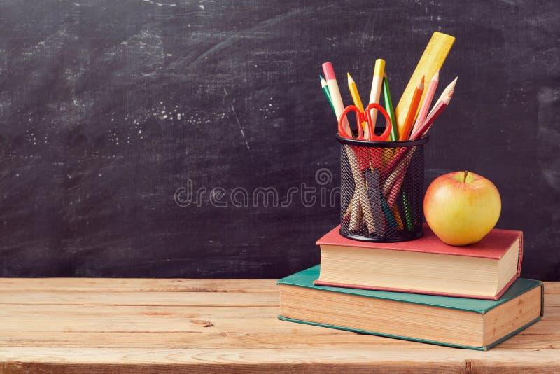 Назад к предпосылке школы с книгами, карандашами и яблоком стоковое фото