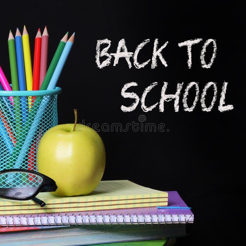 Назад к принципиальной схеме школы. Яблоко, покрашенные карандаши и стекла на куче книг над черной предпосылкой стоковые фото