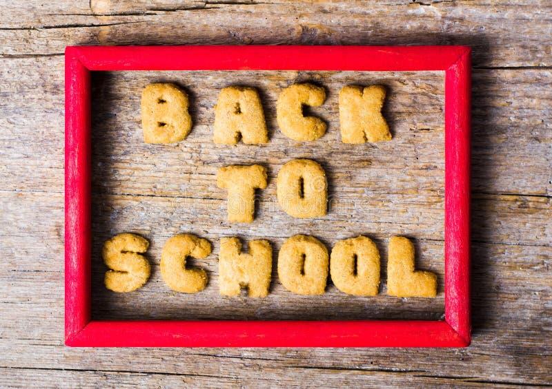 Назад к школе написанной с печеньями на деревянном столе стоковое фото rf
