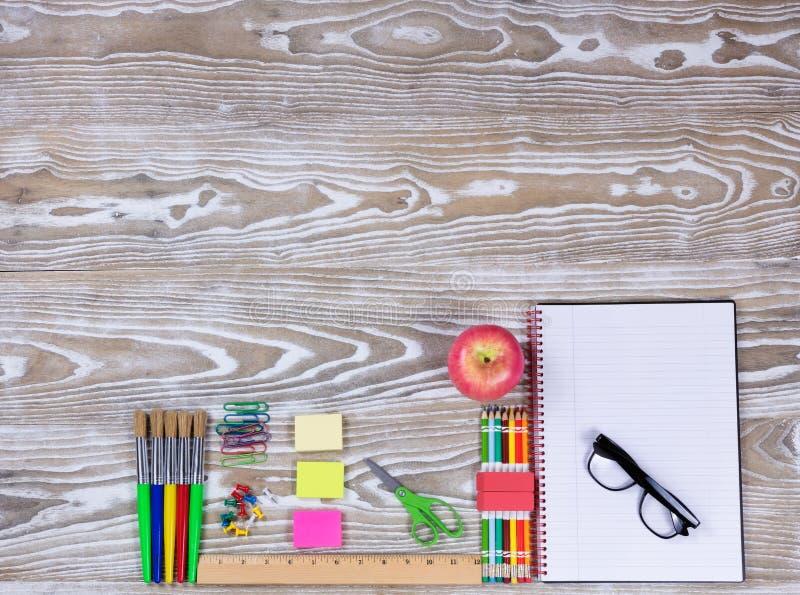 Назад к школьным принадлежностям на увяданной белой деревянной предпосылке стоковое изображение