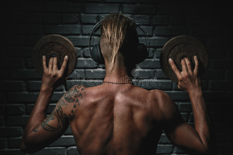 Назад музыки атлетического молодого астетического человека слушая стоковое фото rf