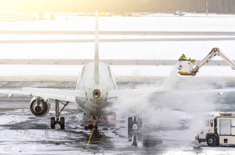 Наземная команда обеспечивает de-замороженность Они распыляют воздушное судно, которое предотвращает возникновение заморозка стоковые изображения