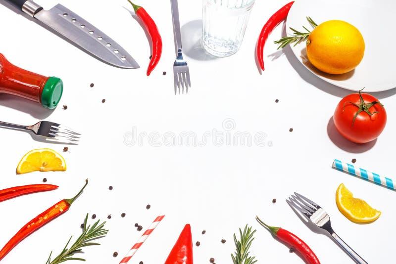 Накаленные докрасна перцы, томаты, розмариновое масло и специи на белой предпосылке Сервировка стола r стоковые фото