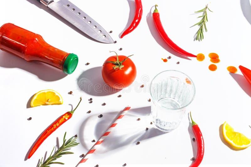 Накаленные докрасна перцы, томаты, розмариновое масло и специи на белой предпосылке Сервировка стола r стоковое изображение