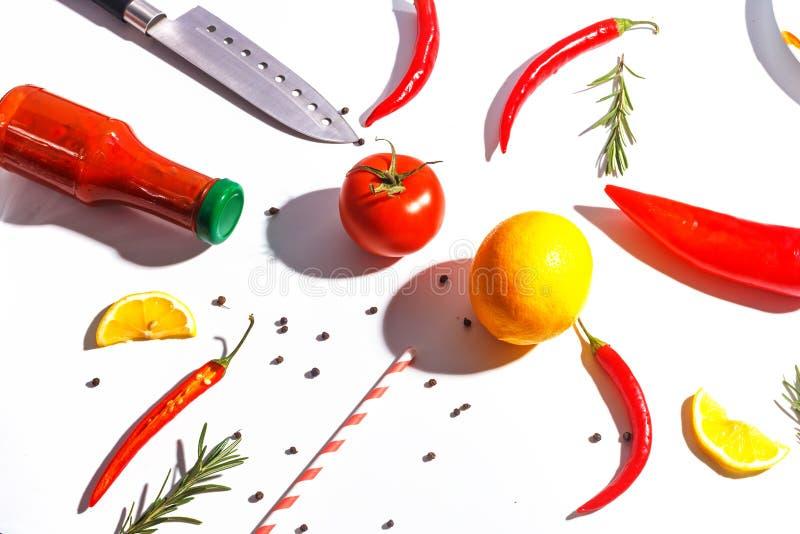 Накаленные докрасна перцы, томаты, розмариновое масло и специи на белой предпосылке Сервировка стола r стоковое фото