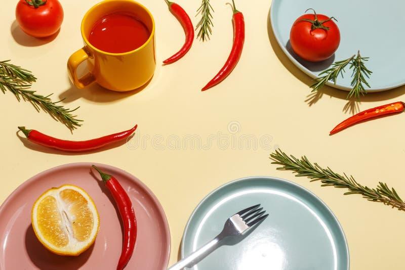 Накаленные докрасна перцы, томаты, розмариновое масло и специи на ligth-желтой предпосылке Сервировка стола r стоковые фотографии rf