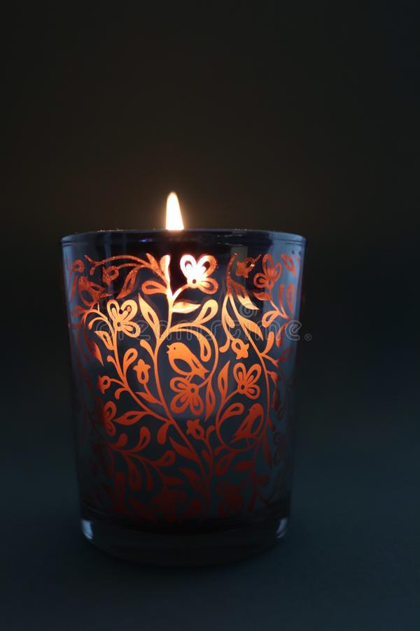 Накаляя выгравированный контейнер свечи пламя создавая теплое зарево стоковое изображение