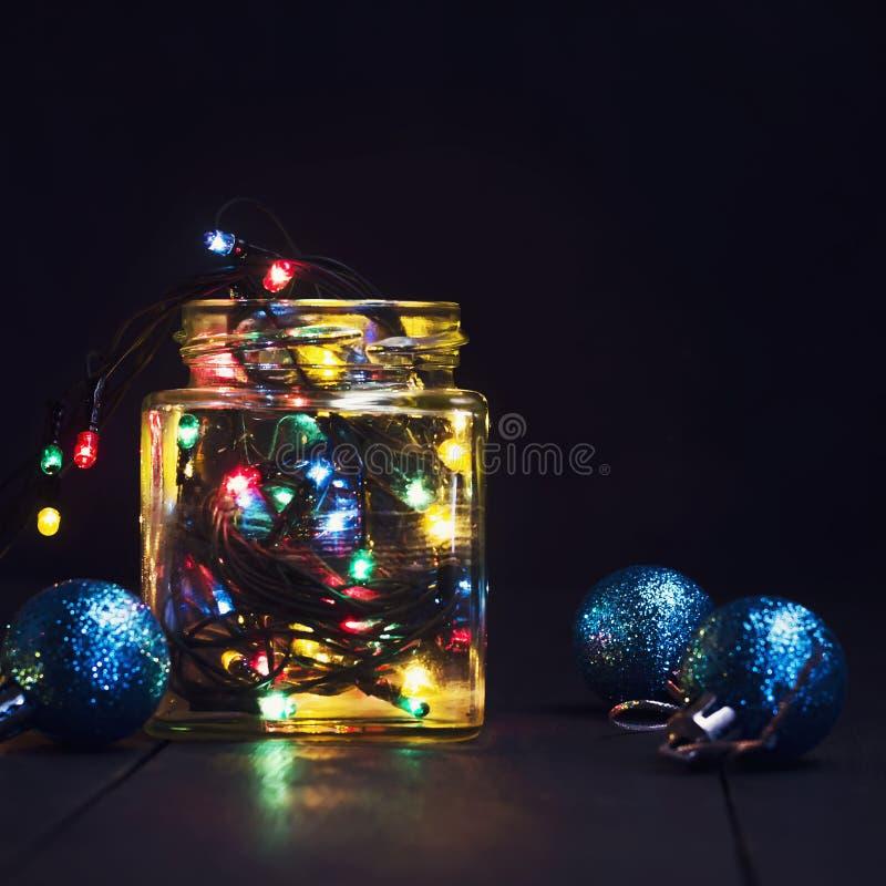 Накаляя гирлянда в стеклянном опарнике и украшения рождества на темной деревянной предпосылке Новый Год, открытка рождества скопи стоковая фотография