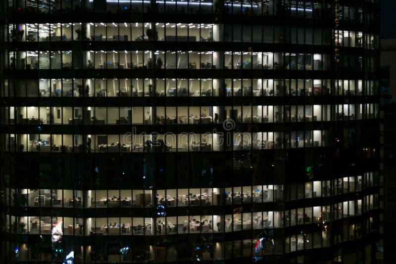 Накаляя окна небоскребов на вечере - взгляде современных офисов в здании стоковое фото rf