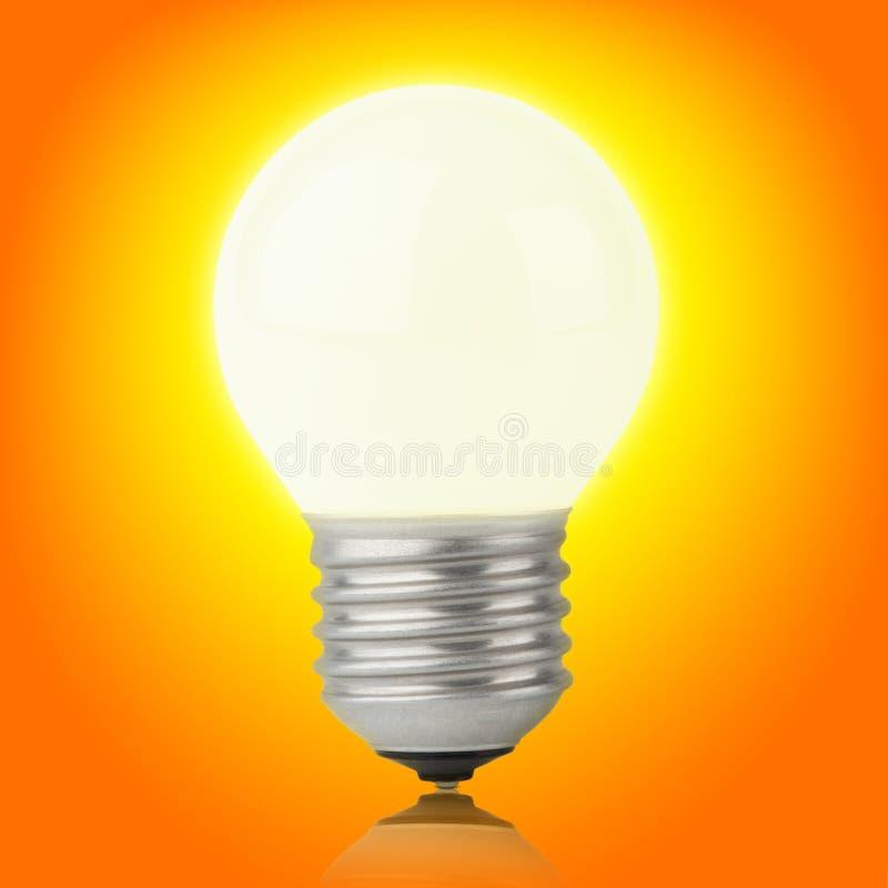 Накаляя раскаленная добела электрическая лампочка на желт-Орандж стоковое фото rf