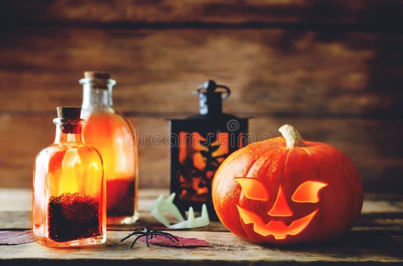 Накаляя тыква с опарниками на темной деревянной предпосылке Жулик хеллоуина стоковые изображения