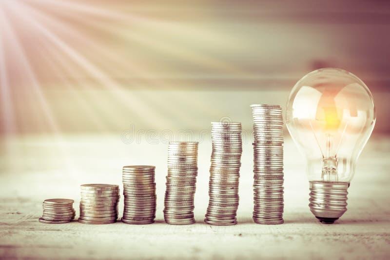 Накаляя электрическая лампочка с монетками кучи стоковые фотографии rf