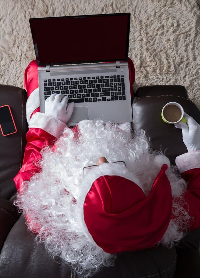 Накладные расходы Санта Клауса ослабляя в софе дома Используя ноутбук f стоковое фото
