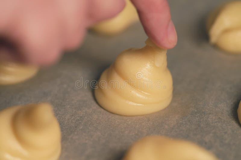 Наклонять тесто choux для profiteroles на бумаге выпечки стоковая фотография rf