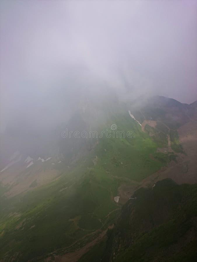 Наклон горы с фуникулерами и горнолыжными склонами на пасмурный летний день, туманом, облаками Черная гора пирамиды, Krasnaya Pol стоковая фотография rf