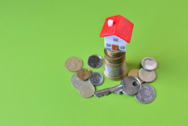 Накопление денег, ипотека или концепция кредита с миниатюрным домом игрушки, стог монеток и ключ стоковые изображения